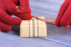 Hands of woman in gloves packaging gift for Christmas or other celebration Stock Photos