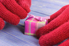 Hands of woman in gloves unpacking gift for Christmas or other celebration Royalty Free Stock Images