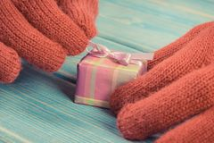 Hands of woman in gloves unpacking gift for Valentines Day or other celebration. Hand of woman in red woolen gloves unpacking and opening gift for Valentine Royalty Free Stock Photo