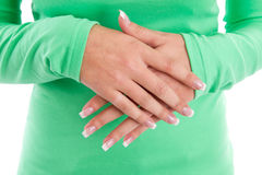 Hands of a woman in a green shirt with French manicure Stock Image