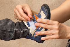 Hands of woman helping child to put shoes Stock Images
