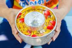 Hands of Woman hold bowl of water mixed with perfume and vivid flowers corolla , Songkran festival of Thailand Royalty Free Stock Photos