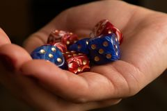 Hands of a woman holding multicolored, plastic dice. Hands of a woman holding gambling, multicolored, plastic dice close-up Stock Image