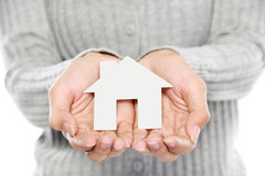 Hands of woman holding paper house. Portrait of Hands of woman holding white paper house Stock Photo