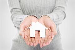Hands of woman holding paper house. Portrait of Hands of woman holding white paper house Stock Image