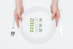 Hands of woman holding plate with green peas, mozzarella, herbs Stock Photos