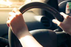 Hands of woman holding steering wheel. Closeup of hands of woman holding steering wheel while Driving Car with sunlight Stock Photos