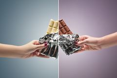 Hands of a woman holding a tile of chocolate. Hands of a woman holding a tiles of brown and white chocolate against the studio. concept of confrontation Stock Images