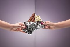 Hands of a woman holding a tile of chocolate. Hands of a woman holding a tiles of brown and white chocolate against the studio. concept of confrontation Stock Image