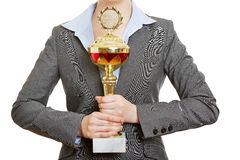 Hands of woman holding trophy cup. Hands of a business woman holding big trophy cup royalty free stock photo