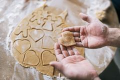 Hands of woman holding unprepared heart-shaped cookie. Royalty Free Stock Photos