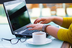 Hands of woman on the keyboard of her laptop computer. Female working on laptop in a street cafe, Royalty Free Stock Photography