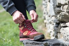 Hands of woman lacing her shoes during a hike Stock Images