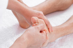 Hands of woman making foot massage Stock Images