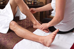 Hands of woman making massage at a man feets Stock Photo