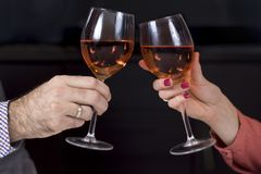 Hands of a woman and a man with wine glasses in hands are toasting. Wine glasses with a dark background stock photos