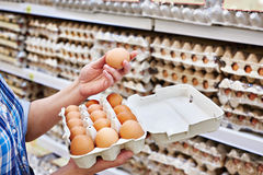 In hands of woman packing eggs in supermarket Stock Image