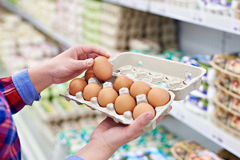 In hands of woman packing eggs in supermarket stock photos
