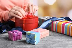 Hands of woman packing presents. For holiday stock photography