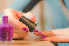 Hands of the woman painting nails bright varnish royalty free stock image