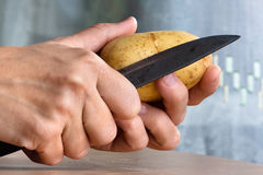 Hands of woman peeling potatoes with knife Stock Photos