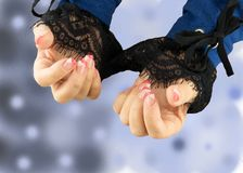 Hands of woman pink white manicured on nails. Bright blue white bokeh blur backround. Black lace on sleeves. Stock Photography