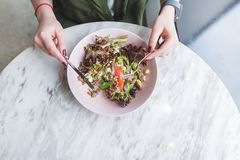 Hands of a woman and a plate of salad. girl eating a salad in a light restaurant at the table overlooks the top royalty free stock images