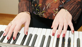 Hands of a woman playing piano Stock Photography