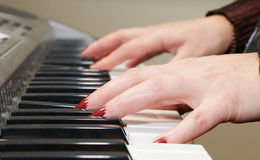 Hands of a woman playing piano Stock Image