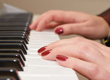 Hands of a woman playing piano Stock Images
