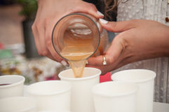 Hands of woman pouring apple juice in plastic cups Stock Photography