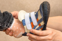 Hands of woman put on shoes child, closeup Stock Photos