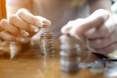 Hand of woman put  a  silver coin on top of two pile for stacking on the wooden table. Hands of woman put  a  silver coin on top of two pile for stacking on the Royalty Free Stock Images