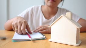 Hands of woman putting coin to House piggy bank saving money for buy home concept.  stock video