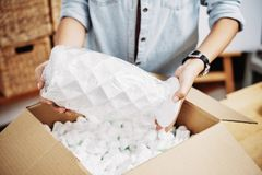 Woman packing vase in box stock photos