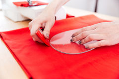 Hands of woman seamstress working with pattern and red textile. Closeup of hands of young woman seamstress working with pattern and red textile on the table Royalty Free Stock Photo
