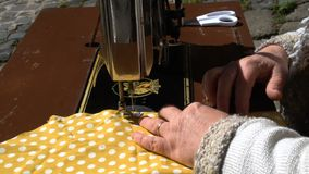Hands of woman on sewing machine lateral closeup slow motion MF stock footage
