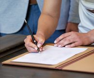 Hands of woman signing documents on wedding day Stock Photo