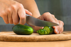 Hands of woman slicing cucumbers on the cutting board Stock Images