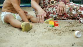 Hands of woman and small child, who sit in the sandbox and play with toys. Concept of motherhood and childcare. Outdoors. Close-up stock footage