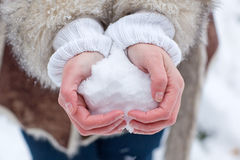 Hands of woman with snow heart stock image
