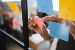 Hands of woman sticking adhesive notes on glass. Close up shot of hands of woman sticking adhesive notes on glass wall in office royalty free stock images