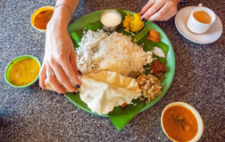 Hands of woman on table with traditional South Indian food thali with rice and spicy vegetables on palm leaf. Royalty Free Stock Image