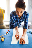 Hands woman Tailor working cutting a roll of fabric on which she Royalty Free Stock Photography