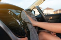 Hands of woman using microfiber fabric to clean up interior of SUV car stock afbeelding