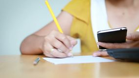 Hands of woman using mobile smart phone and pencil writing on paper metaphor online application and business marketing select focu. S on hand shallow depth of stock video footage