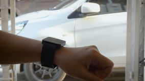 Hands of woman using smart watch to open and close lock and unlock the door of car metaphor remote security application concept.  stock video footage