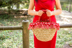 Hands of woman waiting. Female hands holding a bag in a country style made of raffia and red cloth with white flowers, the woman dressed in a red sheath dress is Royalty Free Stock Photo