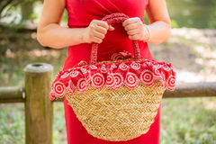 Hands of woman waiting. Female hands holding a bag in a country style made of raffia and red cloth with white flowers, the woman dressed in a red sheath dress is Royalty Free Stock Image