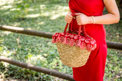 Hands of woman waiting. Female hands holding a bag in a country style made of raffia and red cloth with white flowers, the woman dressed in a red sheath dress is Stock Images
